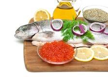 Caviar rouge et truite fraîche sur une planche à découper Photo stock