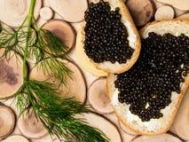 Caviar salé russe noir d'esturgeon de l'Astrakan sur le fond en bois, tranches de pain Casse-cro?te et vacances de luxe image libre de droits