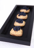 Caviar and salmon canape in tray. Caviar and salmon canape in wood tray Stock Images