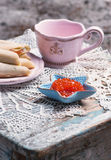 Cup, caviar in small starfish shaped bowl and pancakes with salmon Royalty Free Stock Photos