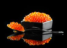 Caviar in a spoon. Salmon caviar in a bowl over black. Closeup trout caviar Stock Photography
