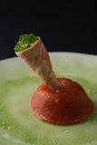 Caviar verde no rolo da bolacha no caviares vermelhos de grãos finos na placa branca, fundo preto Foto de Stock Royalty Free