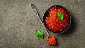 Caviar vermelho delicioso na bacia preta em um fundo concreto escuro Vista superior com espa?o da c?pia Configura??o lisa imagem de stock royalty free