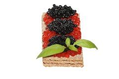 Caviar vermelho e preto com manjericão no pão estaladiço foto de stock