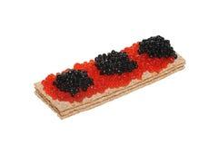 Caviar vermelho e preto no pão estaladiço fotografia de stock royalty free