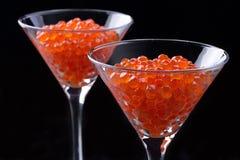 Caviar vermelho em uns copos de vinho no fundo preto Fotografia de Stock Royalty Free