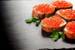 Caviar vermelho no pão preto com manteiga Alimento saudável Aperitivo dos peixes Fundo escuro fotos de stock royalty free
