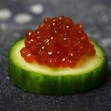 Caviar vermelho no pepino no fundo preto foto de stock royalty free