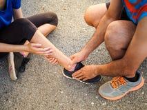 Caviglia storta Giovane donna che soffre da una ferita alla caviglia mentre fotografia stock