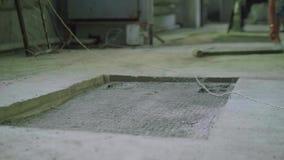 Cavità nell'officina concreta del pavimento Offuschi il punto di vista dell'uomo caucasico che prende la mazza video d archivio