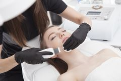 Beautiful woman is having a facial treatment in spa. Cavitation peeling is best treatment for cleaning and moisturizing skin Royalty Free Stock Images