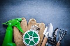 Cavo del giardino dello spruzzatore e strumenti di giardino verdi Fotografia Stock