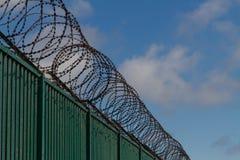 Cavo del rasoio sopra il recinto verde che custodice il terminale di traghetto francese Fotografie Stock