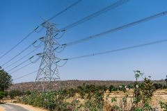 Cavo di griglia di potere sull'azienda agricola della risaia alla rottura rurale di vista di fine della foresta al giorno soleggi Fotografie Stock
