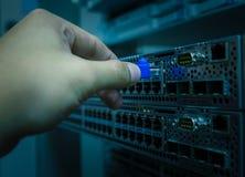 Cavo di lan della spina dell'ingegnere della rete al commutatore di Ethernet Immagine Stock Libera da Diritti
