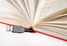 Cavo di USB che attacca da un libro immagine stock