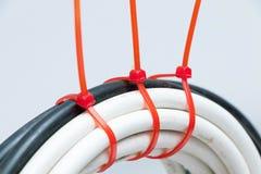 Cavo elettrico del cavo in bianco e nero con i legami rossi dello zip fotografia stock