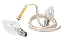 Cavo elettrico e lampadina su priorità bassa bianca Fotografia Stock