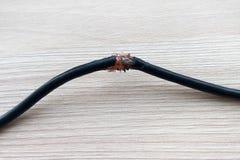 Cavo elettrico nero nocivo sul fondo di legno del pavimento o della tavola Cavo elettrico rotto pericoloso immagini stock libere da diritti