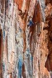 Cavo femminile dello scalatore di montagna che scala roccia naturale Fotografia Stock