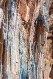 Cavo femminile dello scalatore di montagna che scala roccia naturale Immagine Stock