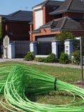 Cavo a fibre ottiche verde accatastato davanti ad alloggio residenziale Fotografie Stock Libere da Diritti