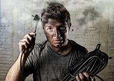 Cavo non addestrato dell'uomo che subisce infortunio elettrico con il fronte bruciato sporco nell'espressione divertente di scoss Immagine Stock