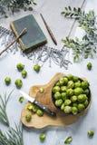 Cavoletti di Bruxelles, libro del cuoco e tagliere immagine stock