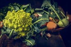 Cavolfiore di Romanesco sul tavolo da cucina rustico con le verdure sopra fondo di legno Immagini Stock