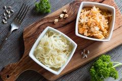 Cavolo e carote fermentati in due ciotole quadrate su una tavola, a Immagini Stock
