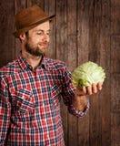 Cavolo felice della tenuta dell'agricoltore su legno rustico Fotografia Stock Libera da Diritti
