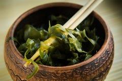 cavolo marino verde del primo piano sui bastoni di legno asiatici in ciotola marrone dell'argilla Fotografie Stock