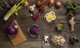 Cavolo rosso, pomodori, aglio e cipolle sulla vecchia tavola di legno Fotografia Stock