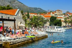 People sunbathing on Cavtat waterfront. CAVTAT, CROATIA - JULY 20, 2017 : People sun bathing and swimming at the seaside with boats moored in Cavtat, Croatia stock photo