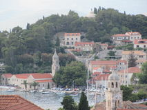 Cavtat, Croatia. Sophisticated Cavtat in Croatia. Showing a church, the clock tower and boats bobbing in the bay. Lots of greenery surrounds the buildings. A Royalty Free Stock Photo