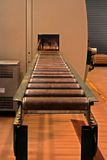 Cawp rollers. Conveyor belt disappearing into machine in a factory Stock Photos