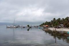 CAYE填缝隙工,伯利兹- 2017年11月20日:Caye填缝隙工海岛在加勒比海 多云早晨和镇静水在码头 库存图片