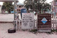 CAYE填缝隙工,伯利兹- 2017年11月18日:Caye填缝隙工海岛在加勒比海 有药物自由区标志的桑迪街 库存照片