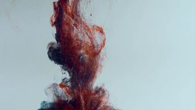 Cayendo y lentamente mezclando la pintura roja y azul en agua,