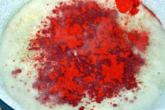 Cayenne pepper. This is a closeup shot of cayenne pepper on a surface of fish soup in preparation Stock Photography