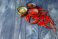 Cayenne pepper and Red peppers on old wooden table Royalty Free Stock Photos