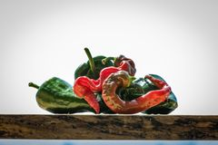 Cayenne and poblano peppers on a wood block with a bright white background. Cayenne and poblano peppers sit on a wood block with a bright white background royalty free stock photos