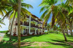Amazing view of Colonial hotel grounds, beautiful inviting retro stylish buildings in tropical garden on blue sky Royalty Free Stock Image