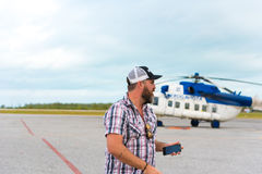 CAYO LARGO, CUBA - MAY 10, 2017: Bearded man in the background of a helicopter at the airport. Copy space for text. CAYO LARGO, CUBA - MAY 10, 2017: Bearded man Stock Photography
