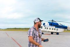 CAYO LARGO, KUBA - 10. MAI 2017: Bärtiger Mann im Hintergrund eines Hubschraubers am Flughafen Kopieren Sie Raum für Text Stockfotografie