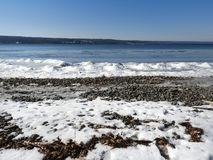 Cayuga Lake frozen wintertime shore. Visited just after a sub-zero cold front passed through the area. Cayuga Lake is the longest of central New York`s glacial royalty free stock photography