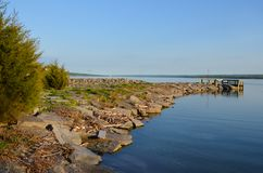 Cayuga Lake rock jetty and dock at Long Point State Park. Long Point State Park on a calm summer day. Part of the southern Finger Lakes region of NYS Stock Photos