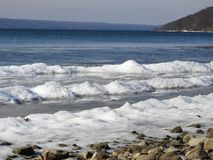 Cayuga Lake winter shore with frozen waves. Rocky winter shoreline of Cayuga Lake with frozen wave line of snow and ice. Cayuga Lake is the longest of central stock photo