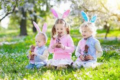 Caza del huevo de Pascua del jardín Los niños comen el chocolate del conejito fotografía de archivo