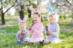 Caza del huevo de Pascua del jardín Los niños comen el chocolate del conejito imagenes de archivo